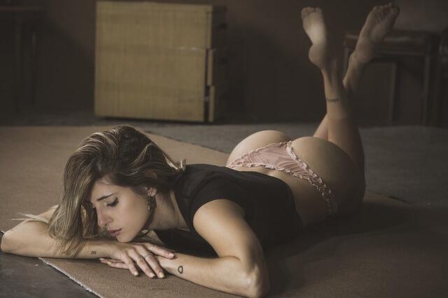 jolie femme en lingerie érotique allongée sur le sol.