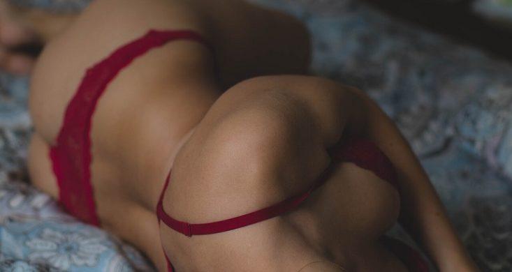 femme en lingerie érotique allongée sur le lit du couple