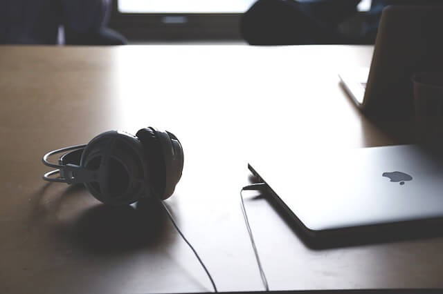 exercice de kegel pour homme: Bureau avec un ordinateur portable et un casque audio